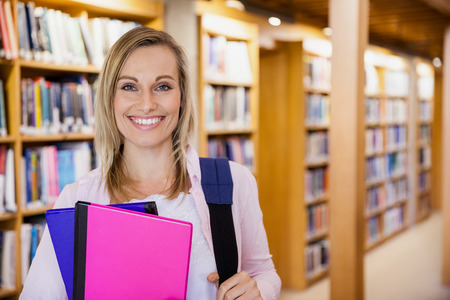 textbooks: Female student holding textbooks in the library at the university Stock Photo