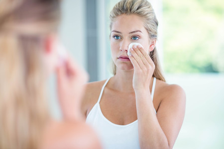 removing make up: Woman wiping her face with cotton pad in the bathroom Stock Photo