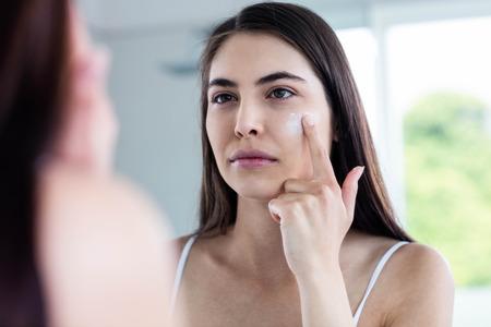 Brunette applying face cream in bathroom 写真素材