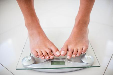Füße der Frau auf Gewichtungsskala zu Hause Standard-Bild