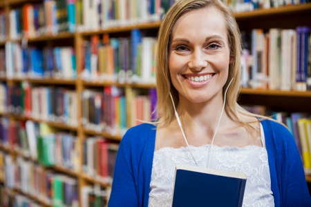 higher intelligence: Smiling female student listening to music in the library at the university