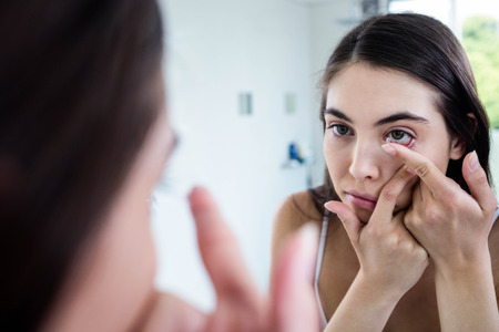 personal grooming: Brunette putting her contact lens in bathroom