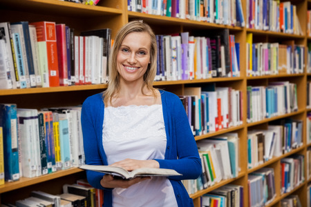 higher intelligence: Happy female student reading a book in the library at the university