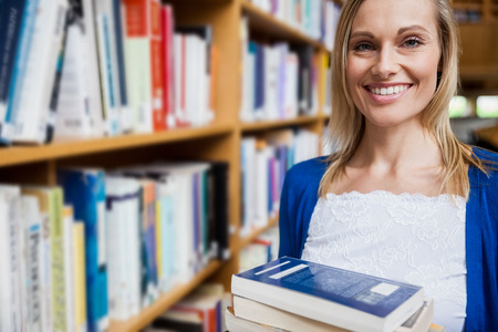 higher intelligence: Happy female student taking books in the library at the university Stock Photo