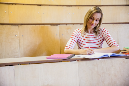 higher intelligence: Focused female student writing notes at the university