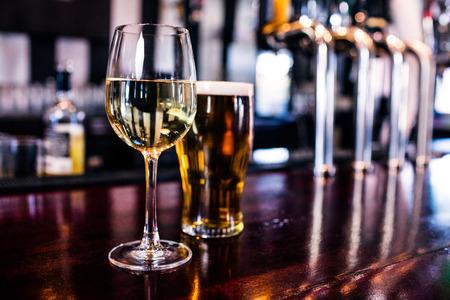 vasos de cerveza: Primer plano de un vaso de vino y una cerveza en un bar Foto de archivo