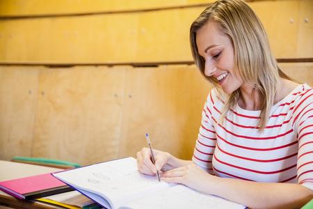 higher intelligence: happy female student writing notes at the university