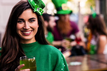 st  patty: Portrait of woman celebrating St Patricks day with friends and drinks