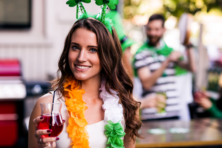 female leprechaun: Portrait of woman celebrating St Patricks day with friends and drinks
