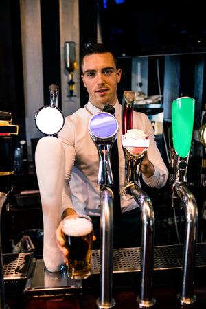 barman: Barman serving a pint of beer in a bar
