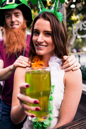 disguised: Disguised woman holding a green pint for St Patricks day