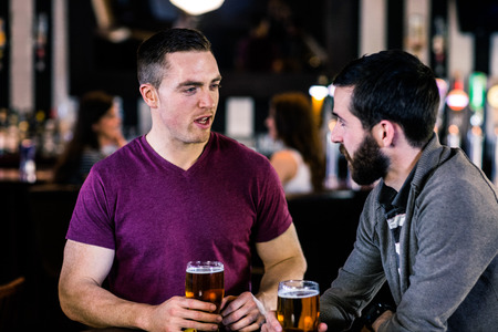 high def: Friends talking and having a pint in a bar Stock Photo