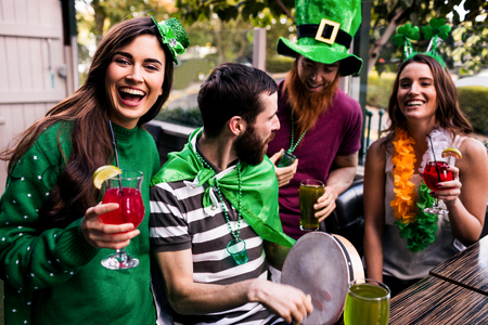 barra: Amigos celebrando el d�a de St Patrick con las bebidas en un bar Foto de archivo