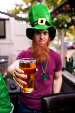 disguised: Disguised man holding a pint for St Patricks day