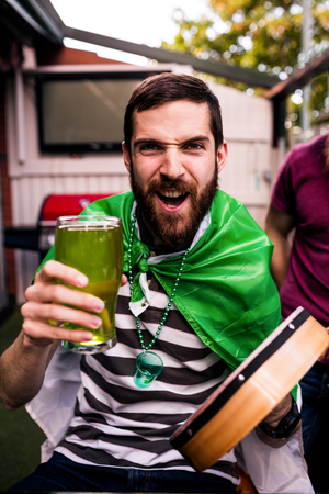 disguised: Disguised man holding a green pint for St Patricks day