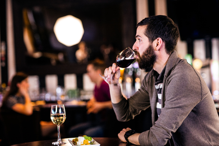 high def: Man having a glass of wine in a bar