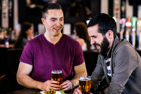 def: Friends having a pint in a bar Stock Photo
