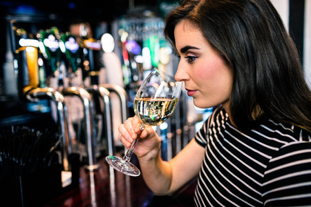 smelling: Attractive woman smelling white wine in the bar