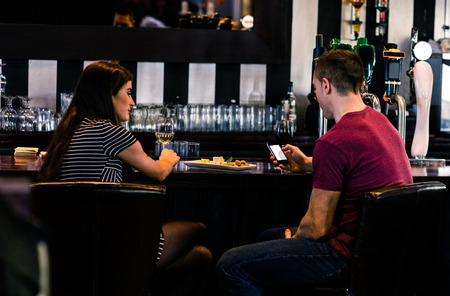 high def: Couple having a glass of wine while man is texting in a bar