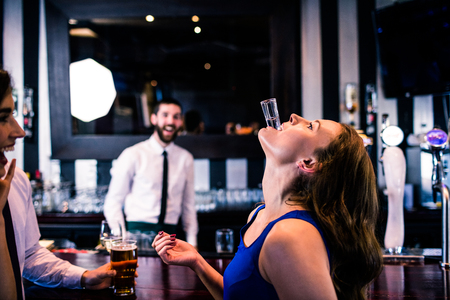 def: Woman playing with her shot in a bar with friends Stock Photo