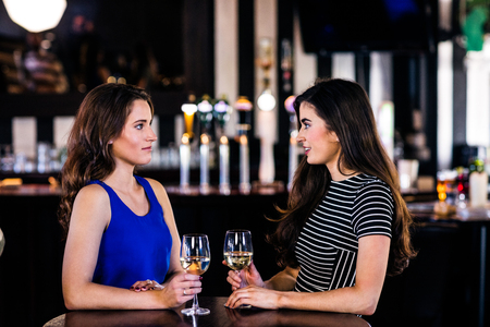 high def: Brunettes talking and holding glasses of white wine in a bar