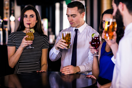 high def: Friends drinking cocktails and beers in a bar