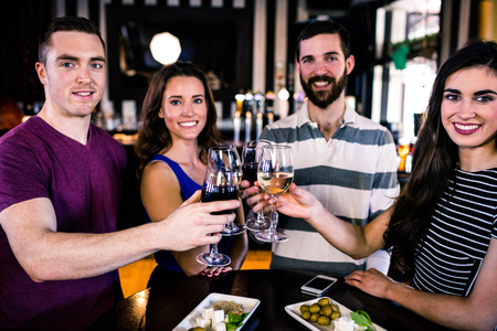 high def: Group of friends toasting with a glass of wine in a bar