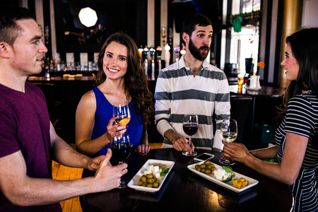high def: Friends having an aperitif with wine in a bar