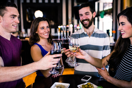 Group of friends having a glass of wine in a bar Stock Photo