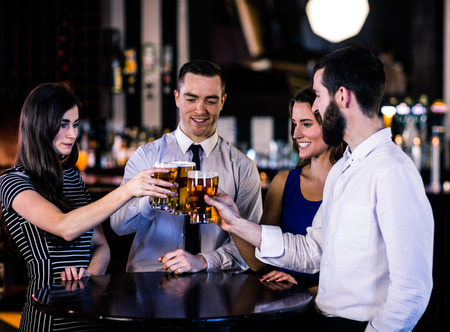 high def: Friends toasting with a beer in a bar Stock Photo