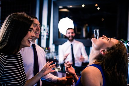 high def: Woman playing with her shot in a bar with friends Stock Photo