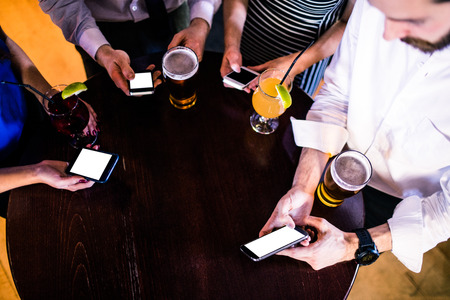 high def: Group of friends texting and having a drink in a bar Stock Photo