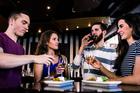 high def: Group of friends having a glass of wine in a bar Stock Photo