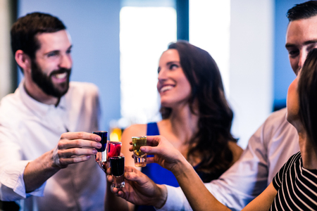 high def: Friends toasting with alcohol shots in a bar