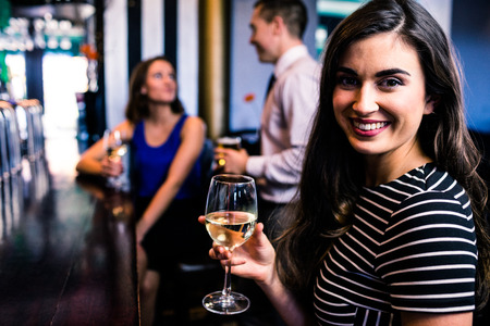 def: Portrait of woman having a drink with friends in a bar