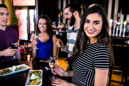 high def: Portrait of woman having an aperitif with friends in a bar Stock Photo