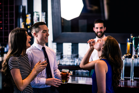 high def: Woman having a shot with friends in a bar Stock Photo