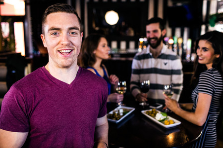 high def: Portrait of man having a drink with friends in a bar