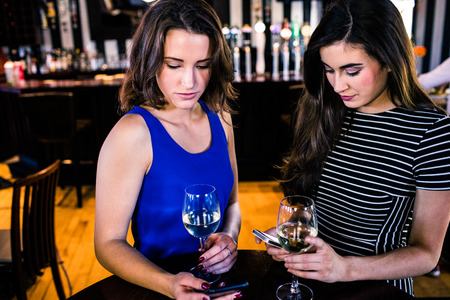 high def: Friends texting and having a glass of wine in a bar Stock Photo