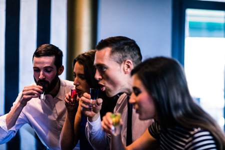high def: Friends drinking alcohol shots in a bar Stock Photo