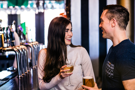 couple talking: Cute couple talking and having a drink in a bar Stock Photo