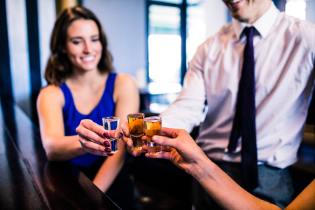 high def: Friends toasting with shots in a bar