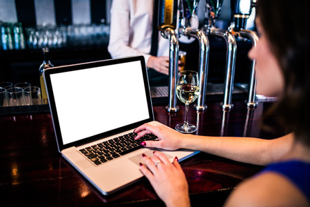 evening wear: Woman using laptop and having a drink in a bar Stock Photo