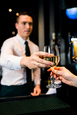 barman: Barman giving a drink to customer in a bar