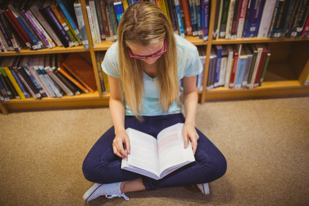 read: Blonde student reading while sitting on books in library Stock Photo