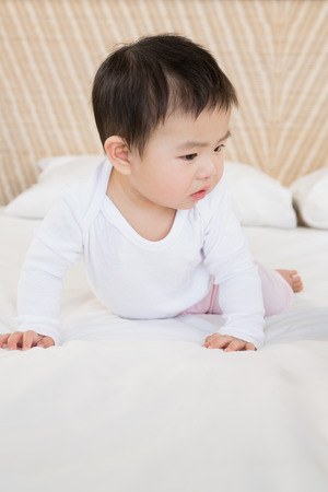 babygro: Cute baby on bed looking down