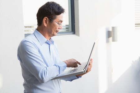 concentrated: Concentrated man using laptop at home