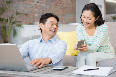 Smiling woman showing smartphone to her husband in the living room Stock Photo