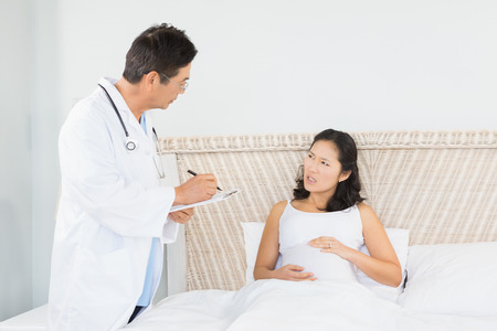 seniors suffering painful illness: Doctor visiting pregnant woman in bedroom