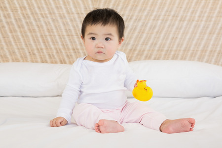 babygro: Cute baby holding plastic duck on bed Stock Photo